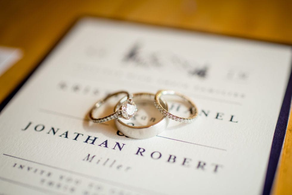 detail photo of wedding rings on top of invitation