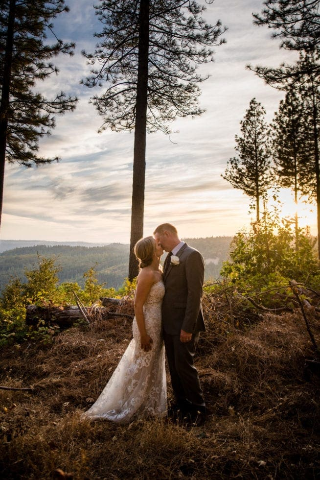 bride and groom kiss with trees and mountains in background at mountain shadows retreat in foresthill, ca