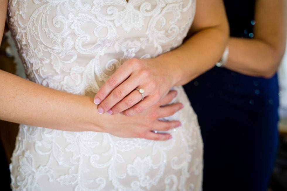 close up of bride's ring and wedding dress