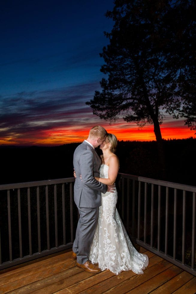 bride and groom standing in front of sky during sunset at mountain shadows retreat in foresthill, ca