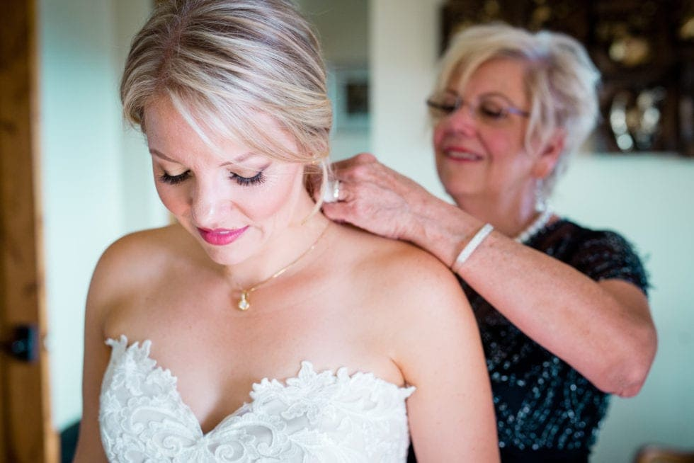 mother of bride helping bride put on a necklace