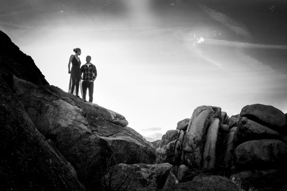 couple standing on top of a large rock