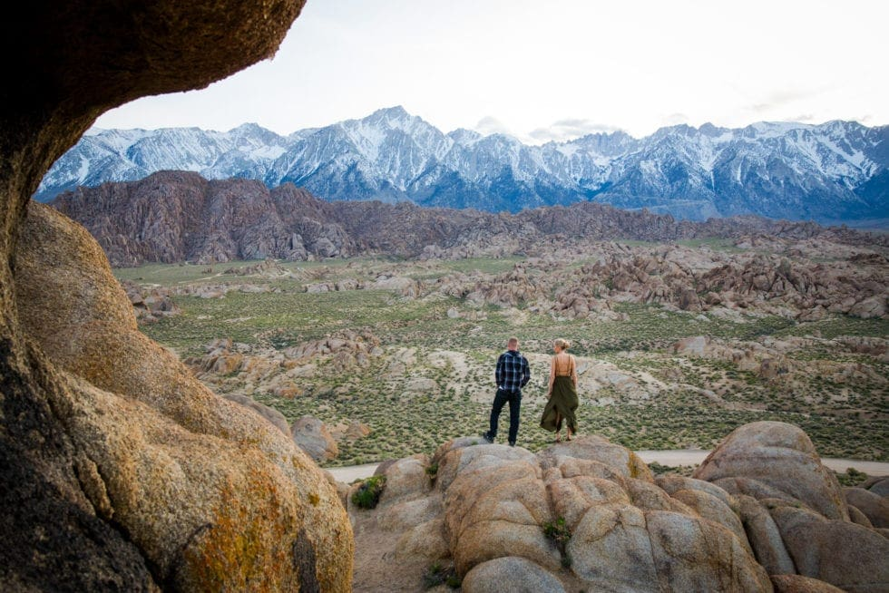 couple standing next to each other and looking out over valley at Alabama Hills in California