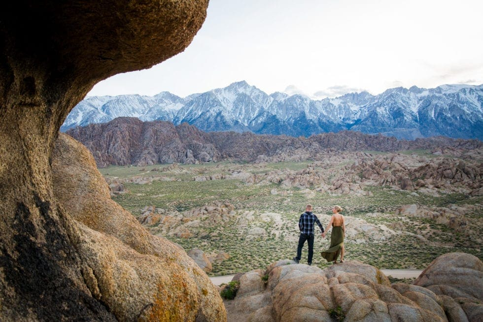 couple holding hands and looking out over valley at Alabama Hills in California