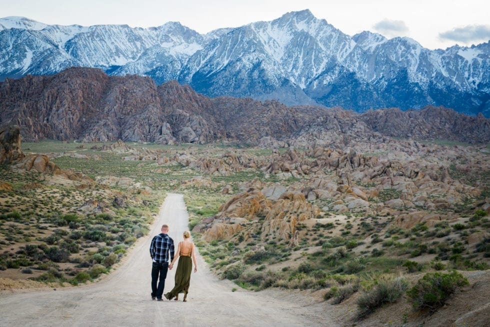 couple holding hands and walking down dirt road toward mountains in Alabama Hills in California