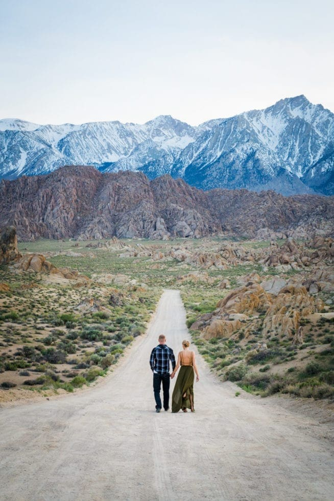 couple walking on dirt road towards mountains in the distance at Alabama Hills in California