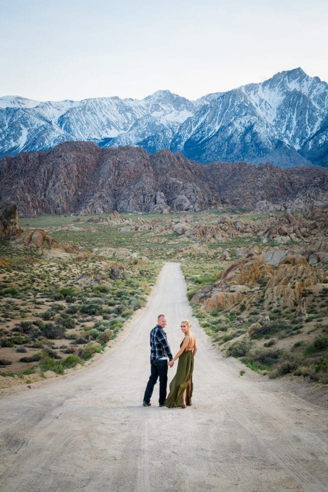 couple holding hands and standing in dirt road in front of mountains at Alabama Hills in California