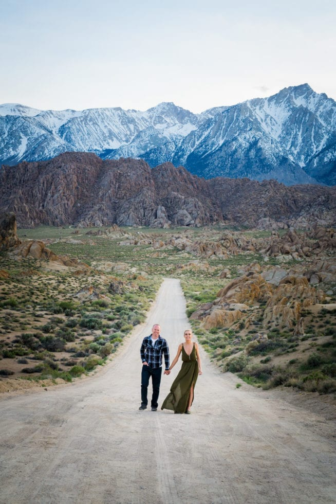 couple holding hands in dirt road in front of mountains at Alabama Hills in California