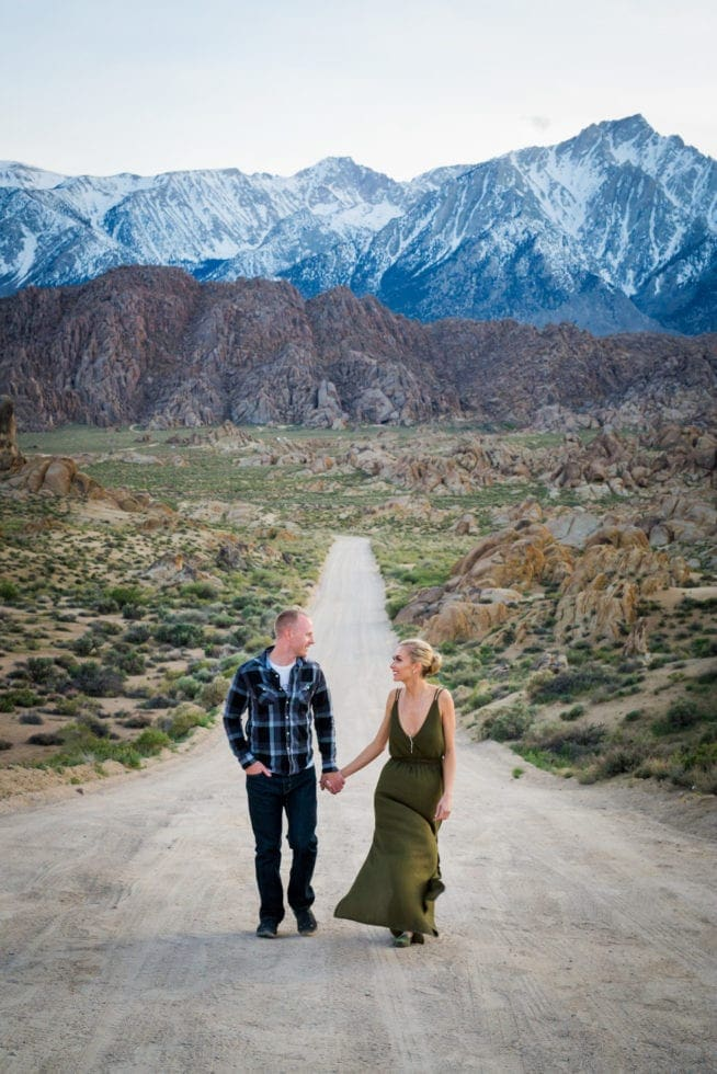 couple holding hands while walking toward camera on dirt road with mountains in the background at Alabama Hills in California