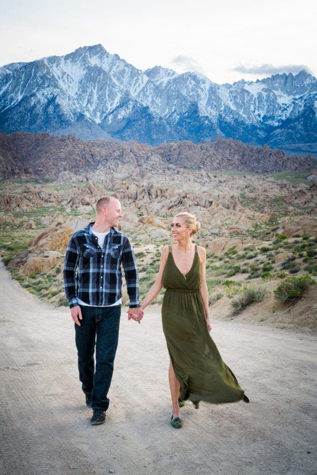 couple looking at each other while walking toward camera on dirt road with mountains in the background at Alabama Hills in California