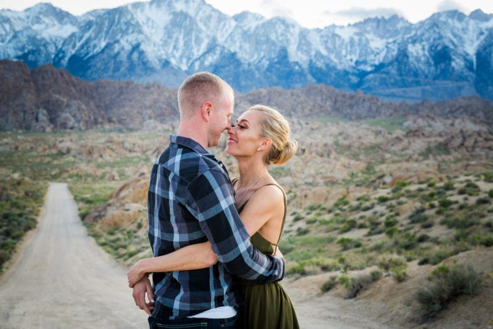 couple embracing in front of dirt road and mountains at Alabama Hills in California