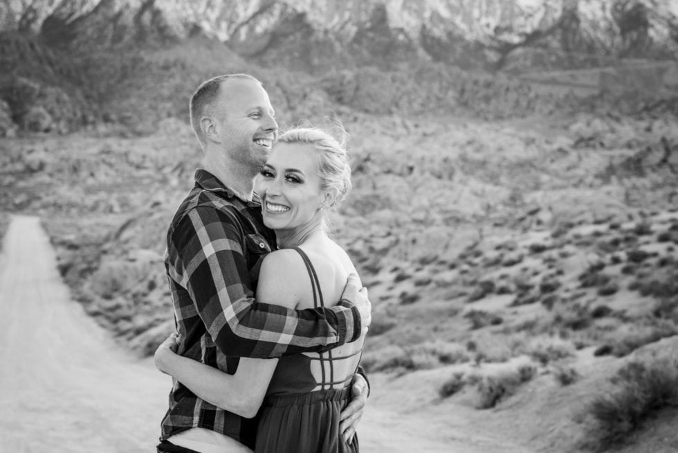 couple hugging and laughing in front of dirt road and mountains