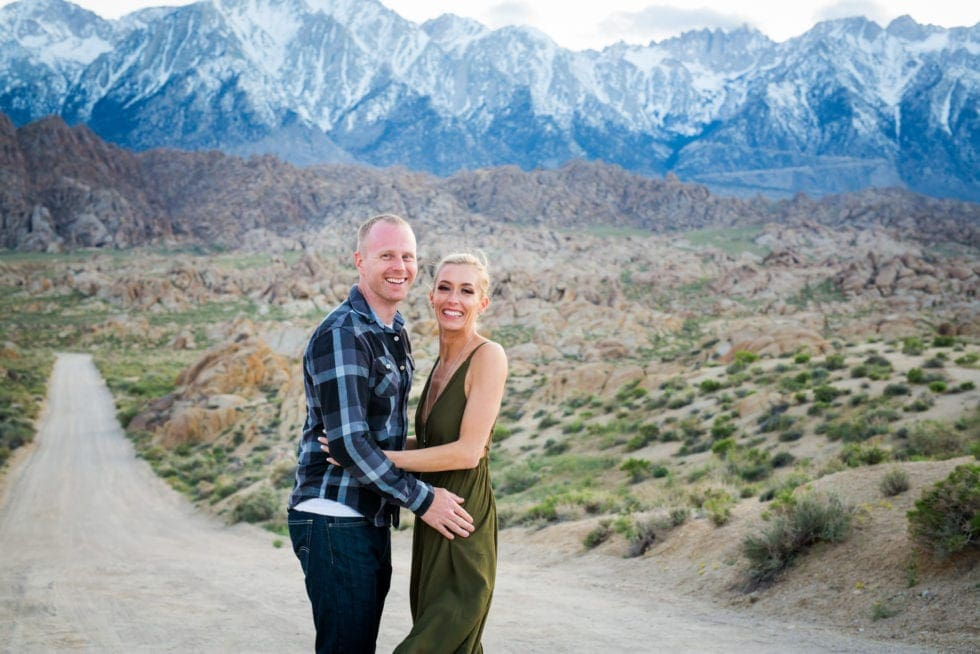 couple laughing in front of dirt road and mountains at Alabama Hills in California