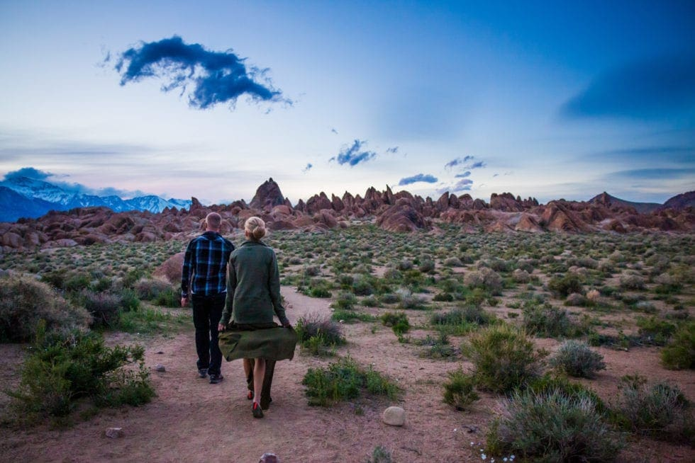 couple walking toward large rocks at dusk