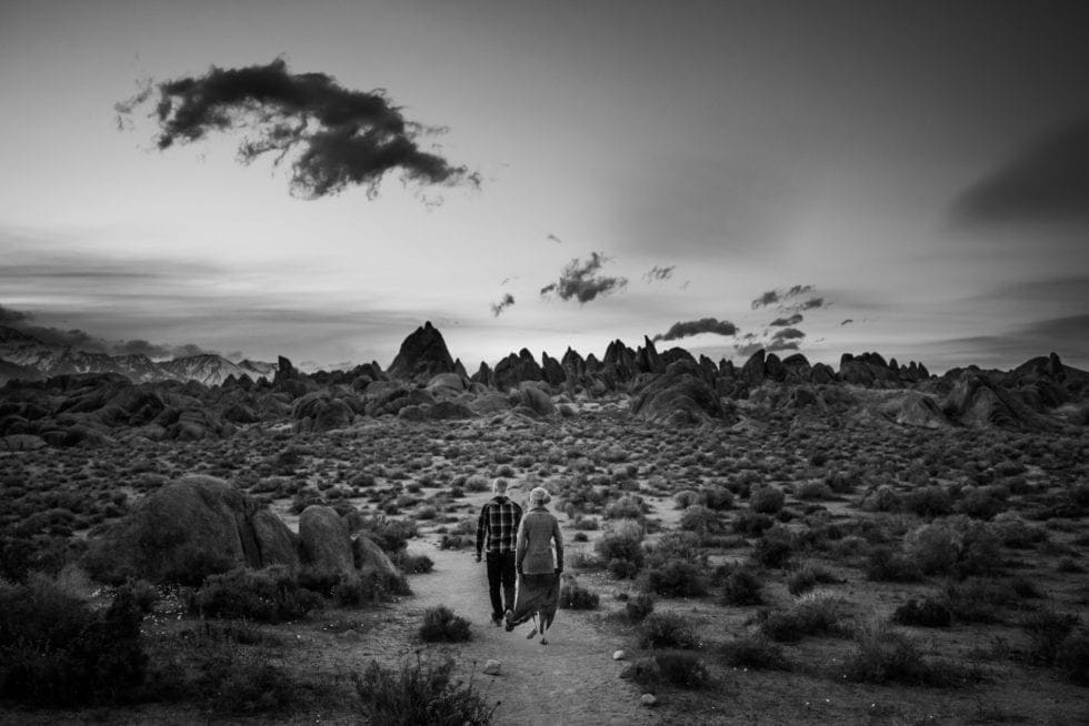couple walking in valley toward large rock formations