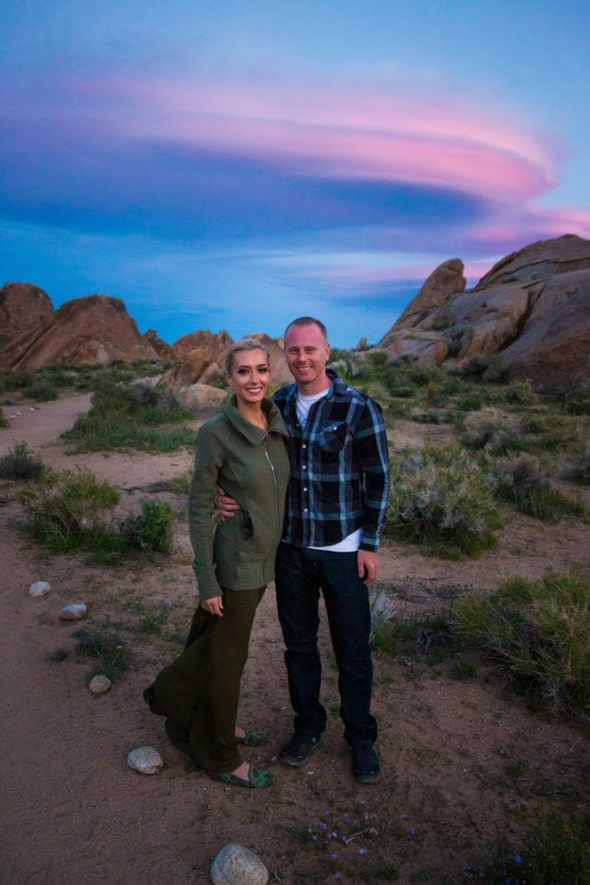 couple standing in front of sunset pink cloud