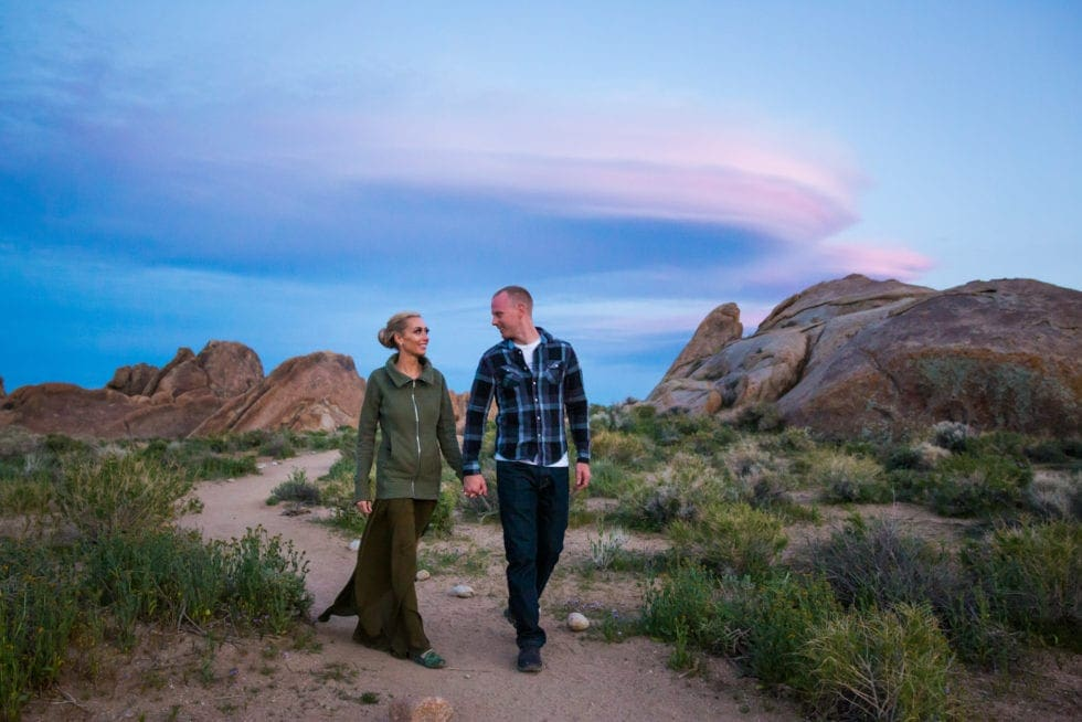 couple holding hands in front of rocks and pink clouds