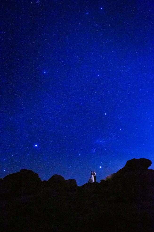 bride and groom standing in front of the night sky