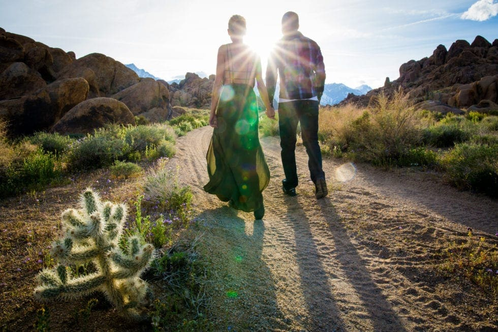 couple holding hands and walking towards sun on dirt road