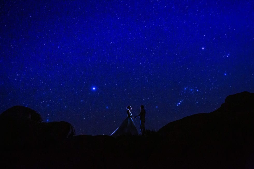bride and groom holding hands with the night sky in the background