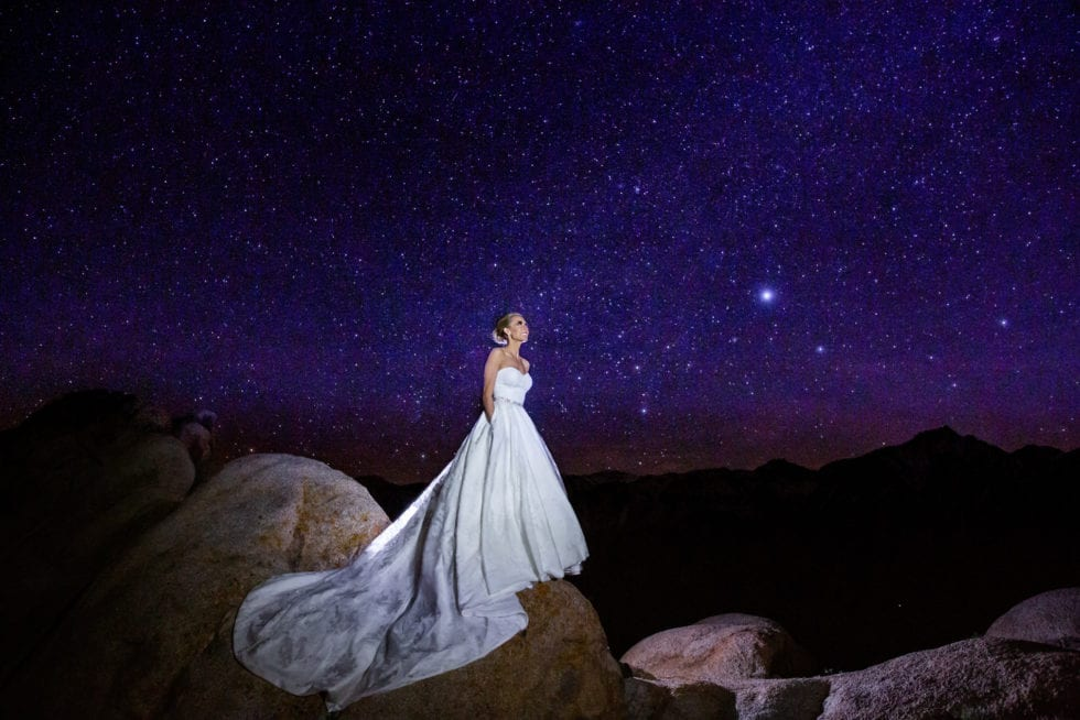 bride standing on a large rock in front of the night sky