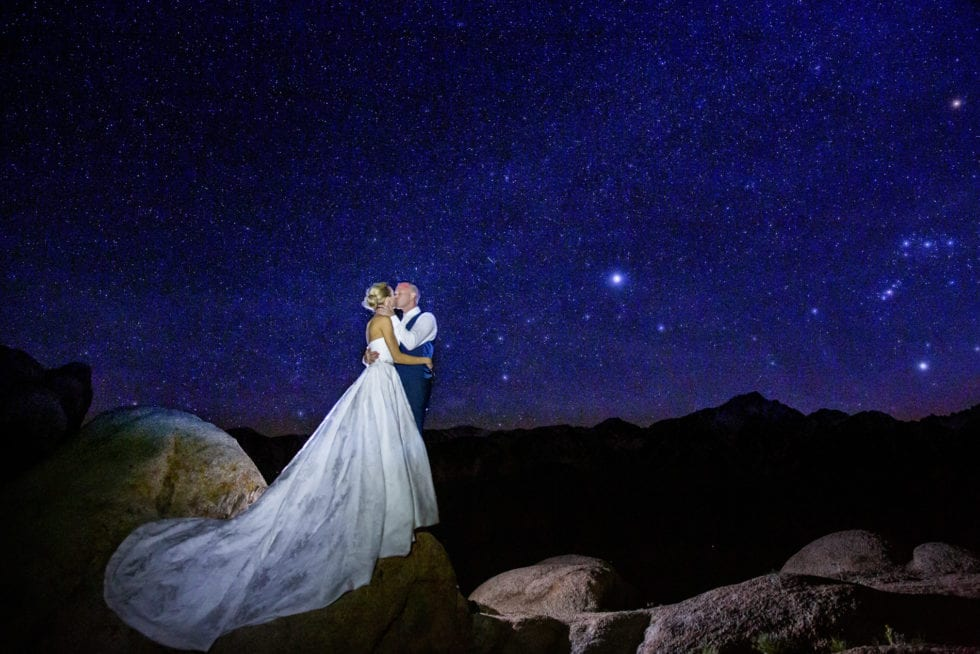 bride and groom kissing on top of large rock with stars in the background
