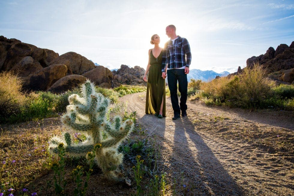 couple holding hands and walking toward camera on dirt road