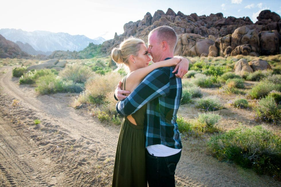 couple embracing and looking into each other's eyes in front of rocky mountain and dirty road