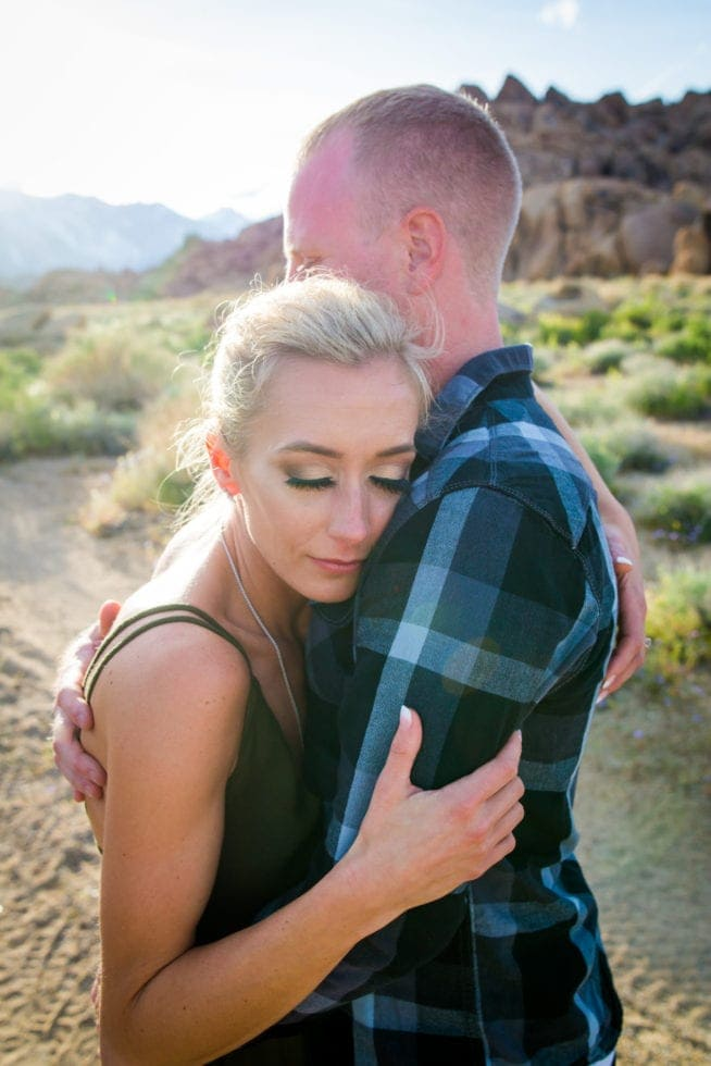 couple embracing with rocky mountain and greenery in background