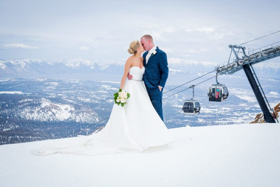 bride and groom kissing while standing in front of ski lift on mammoth mountain