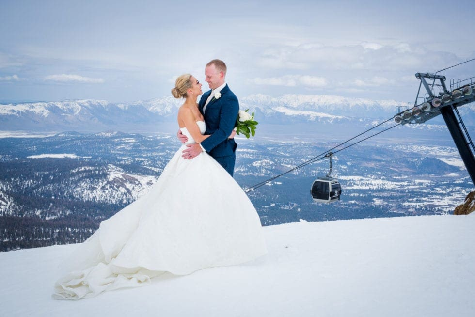 bride and groom looking at each other while standing in front of ski lift on mammoth mountain