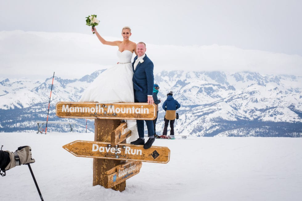 bride and groom standing on top of mammoth mountain sign with snow