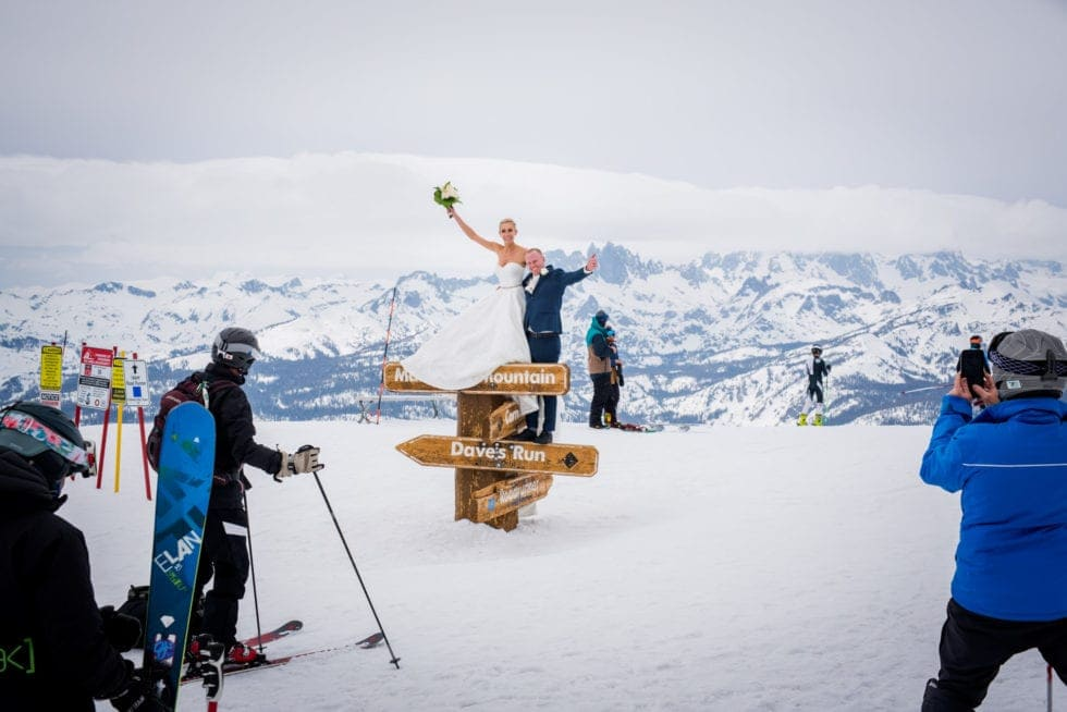 bride and groom standing on top of mammoth mountain sign while skiers take photos