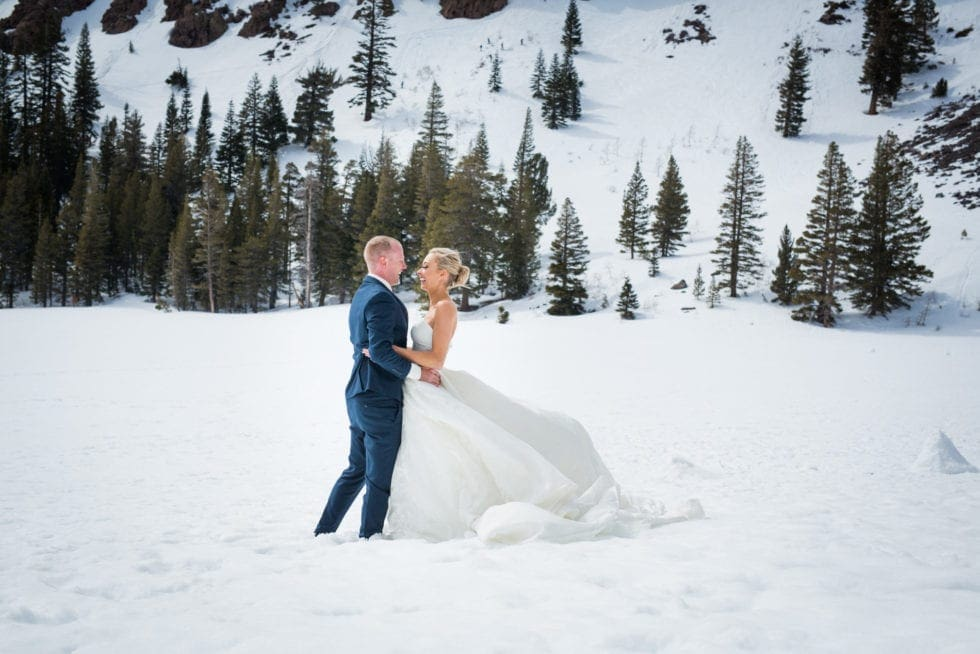 bride and groom looking at each other and standing in front of a snowy mountain