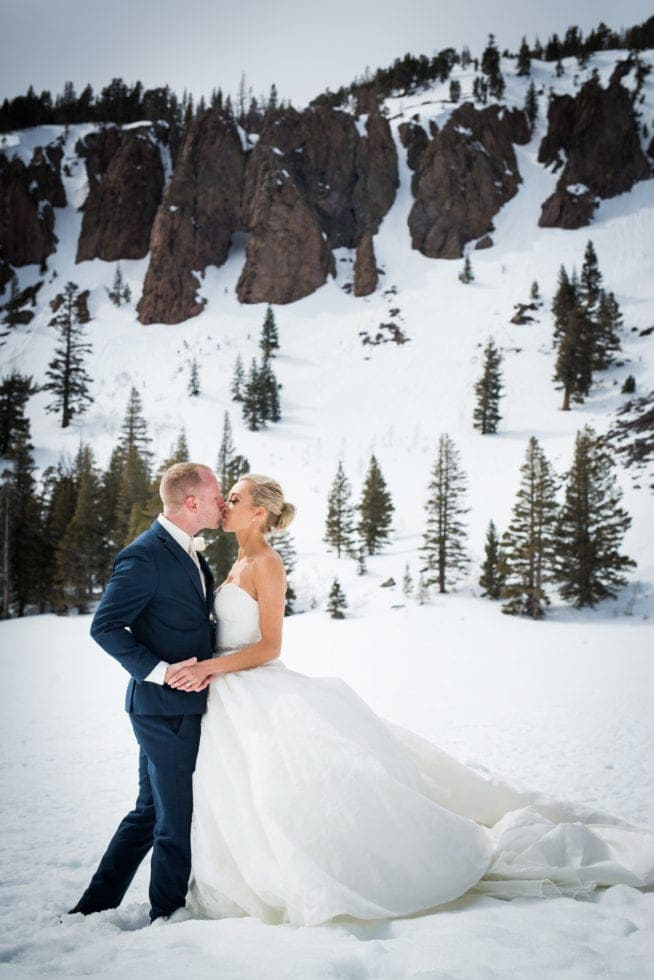 bride and groom kissing while standing in front of a snowy mountain