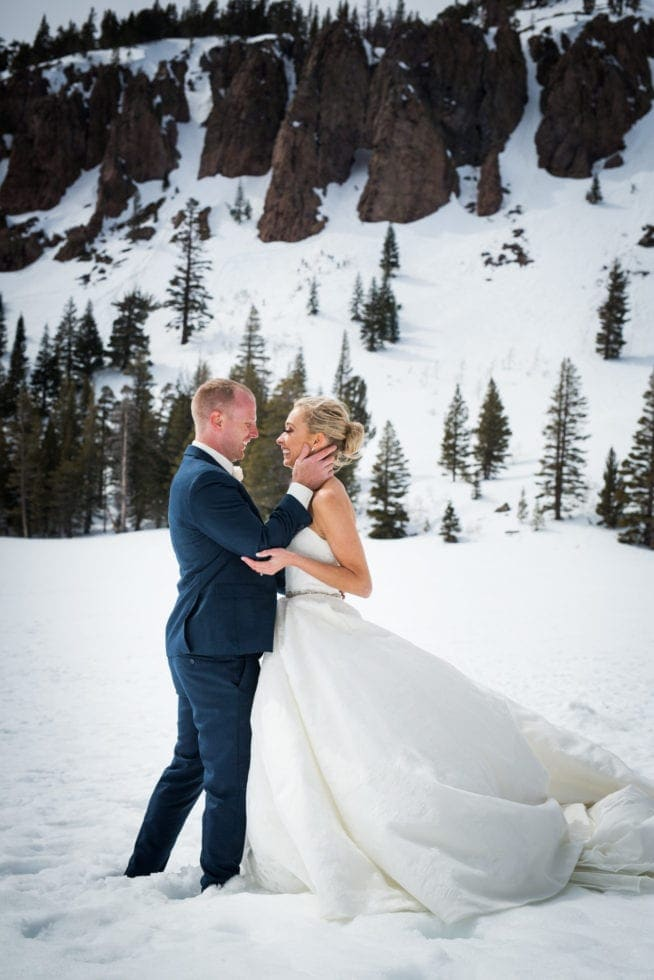 bride and groom looking at each other while standing in front of a snowy mountain