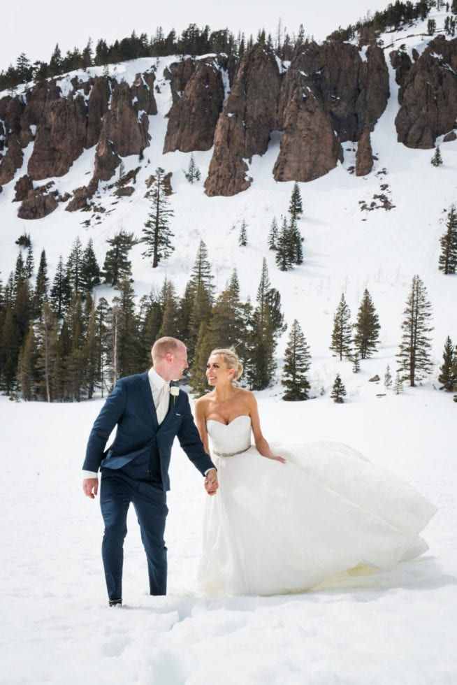 bride and groom holding hands and looking at each other while walking through snow