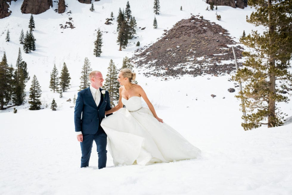 bride and groom laughing while standing in the snow