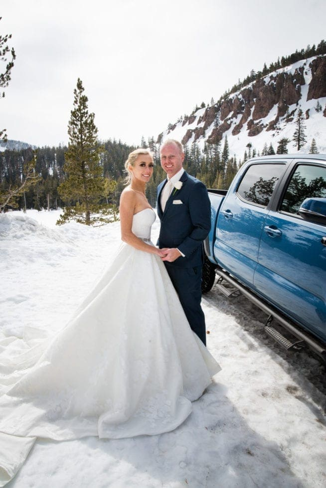 bride and groom smiling while standing in front of a truck in the snow