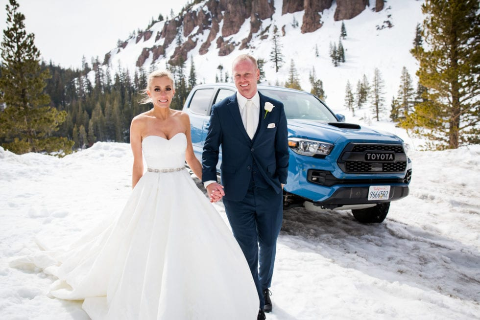 bride and groom standing in front of truck and snowy mountain