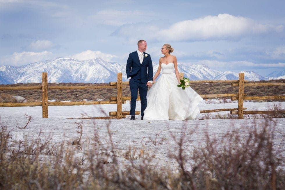 bride and groom holding hands and looking at each other standing in front of snowy mountain
