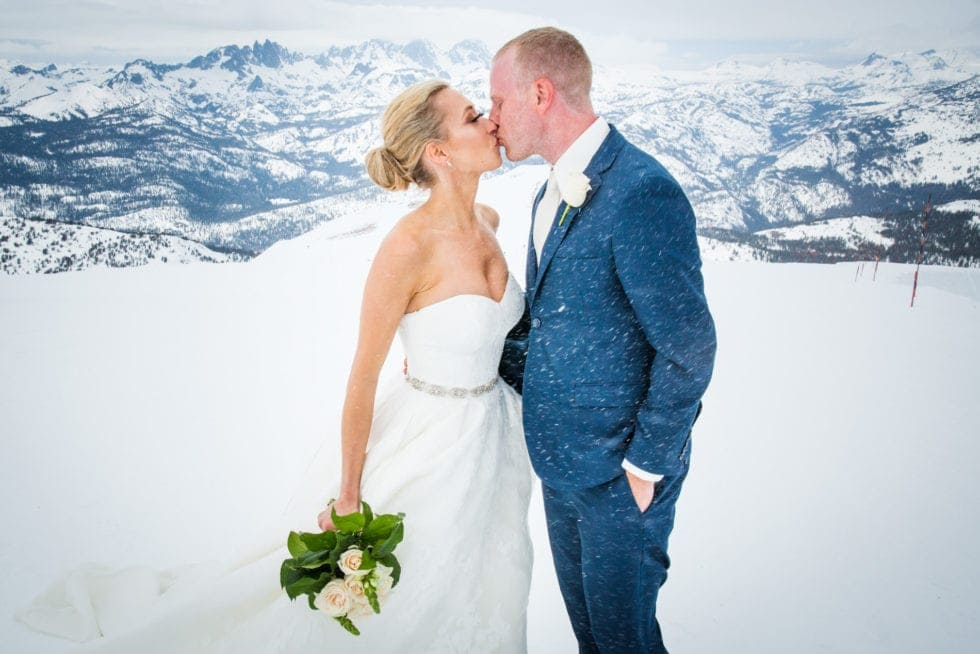 bride and groom kissing on mammoth mountain while it snows