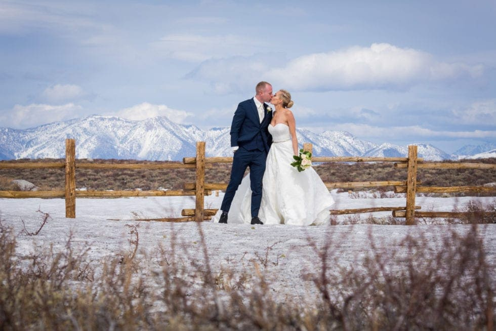 bride and groom kissing standing in front of snowy mountain