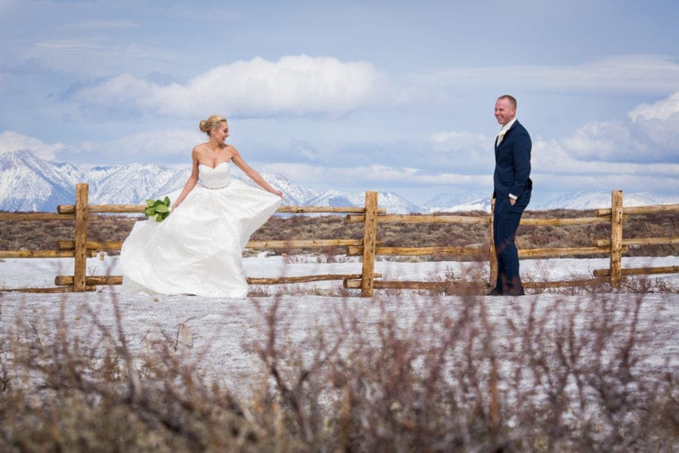 bride and groom standing in front of snowy mountain