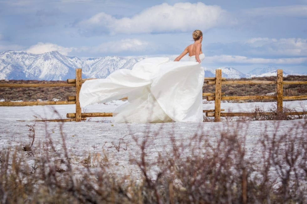 bride standing in the wind in front of snowy mountain