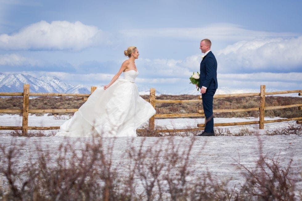 bride and groom looking at each other while standing in front of snow covered mountain