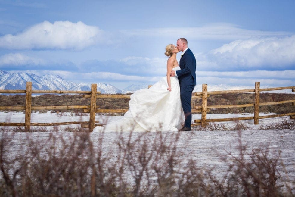 bride and groom kissing while standing in front of snow covered mountain