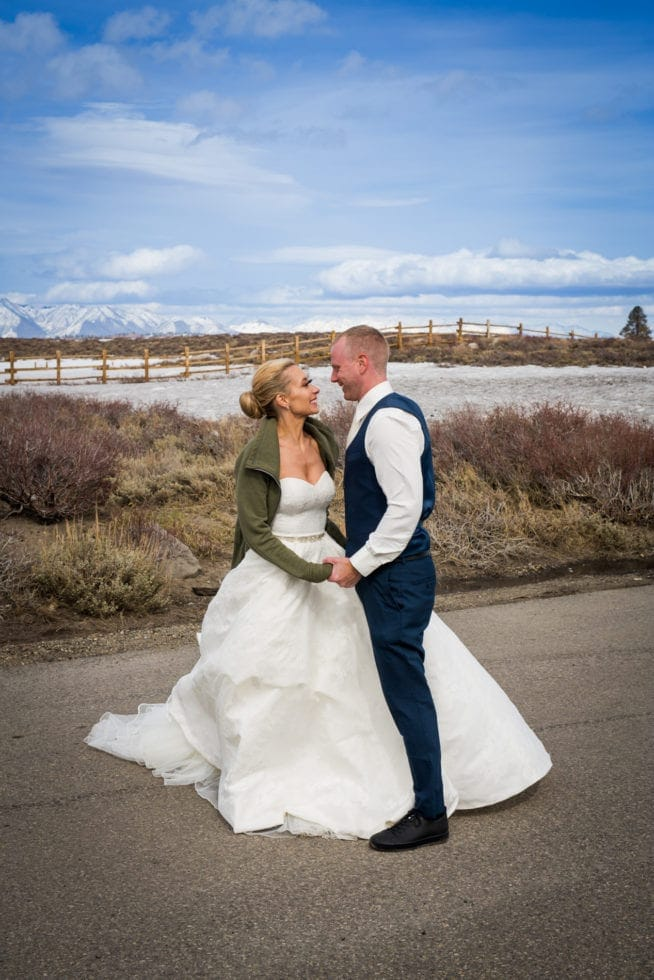 bride and groom looking at each other and holding hands while standing in the road in front of snow covered mountain