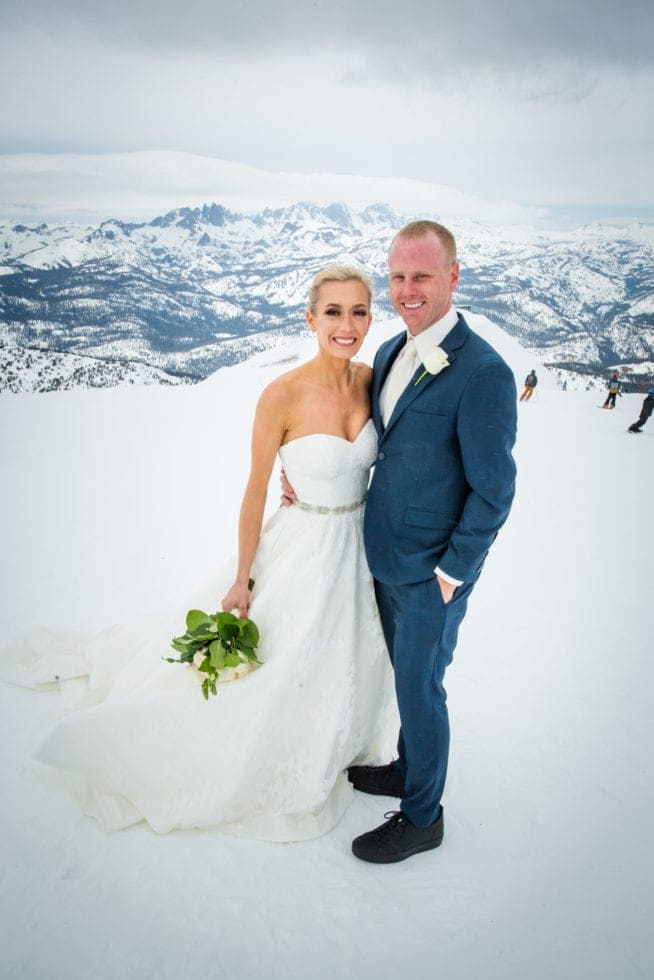 bride and groom looking at camera while standing on mammoth mountain with snowy mountain and skiers in background