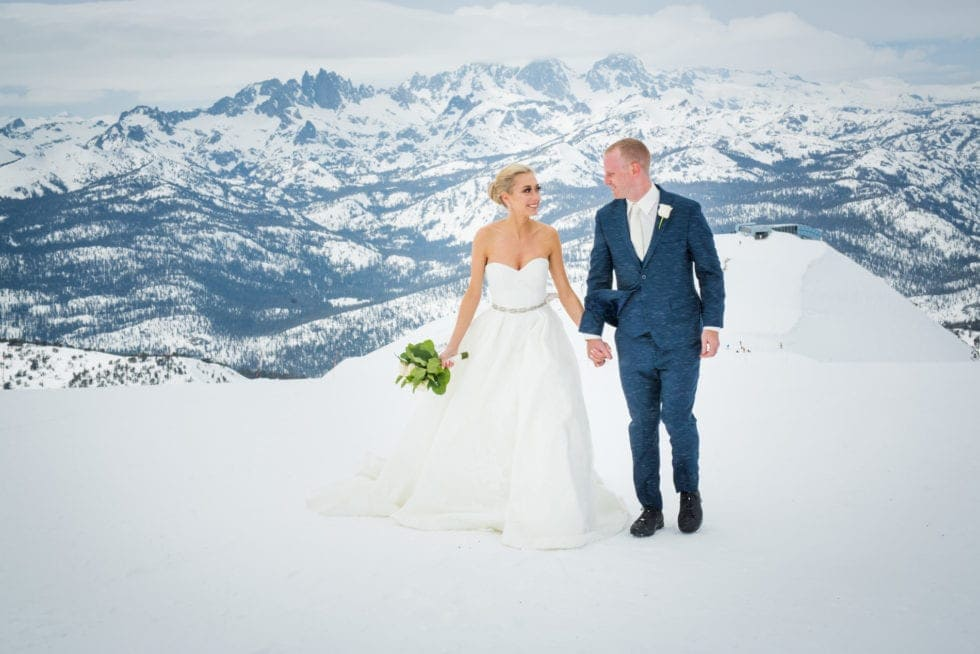 bride and groom walking toward camera while standing on mammoth mountain with snowy mountain in background